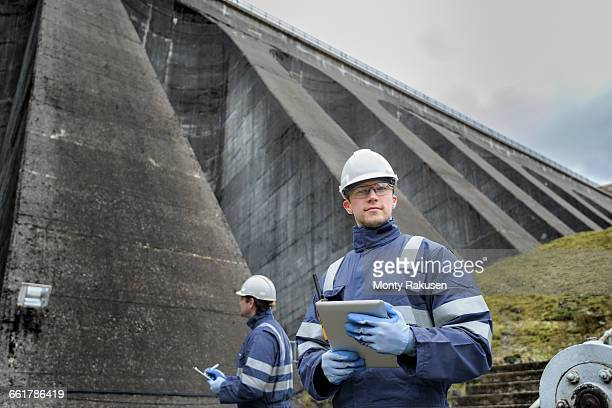 portrait of worker at foot of dam at hydroelectric power station - hydroelectric power stock pictures, royalty-free photos & images
