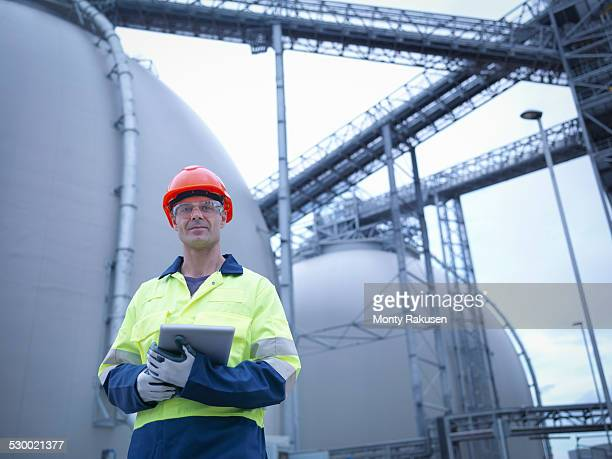 Portrait of worker holding digital tablet at biomass facility