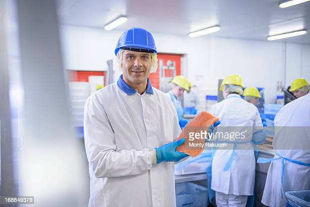 Portrait of worker holding salmon fillet in food factory, smiling