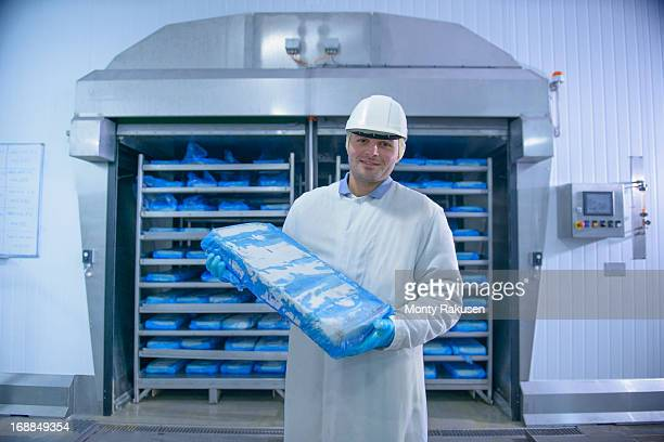 Portrait of worker in factory freezer holding frozen fish, smiling