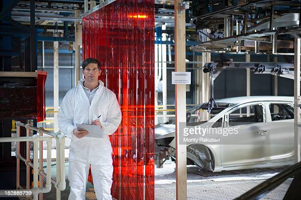 portrait of worker inspecting car body in car factory - white suit stock pictures, royalty-free photos & images