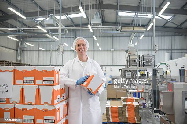 Portrait of worker on packing line in biscuit factory, smiling