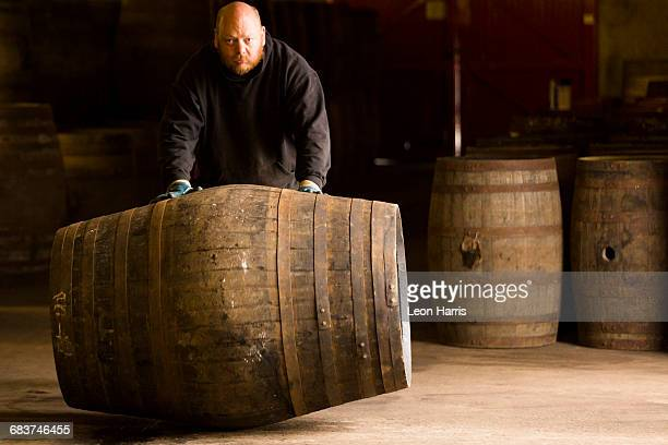 Portrait of worker rolling whisky cask in whisky distillery