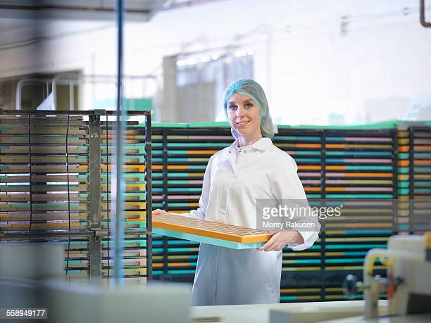 Portrait of worker stacking moulds in chocolate factory