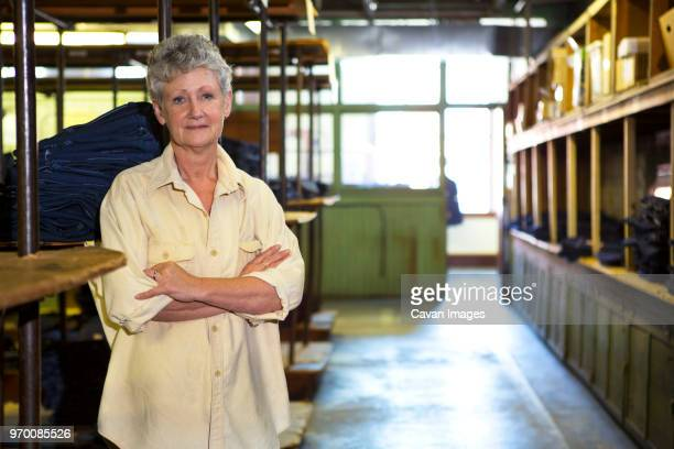 portrait of worker standing in factory warehouse - weibliche angestellte stock-fotos und bilder
