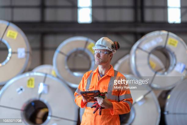 portrait of worker using digital tablet by rows of sheet steel in storage at port - longshoremen stock pictures, royalty-free photos & images