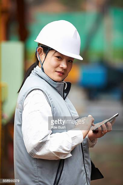 Portrait of worker using smartphone at shipyard, GoSeong-gun, South Korea