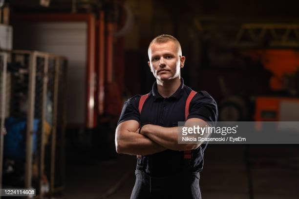 portrait of worker with arms crossed standing in factory - suspenders stock pictures, royalty-free photos & images