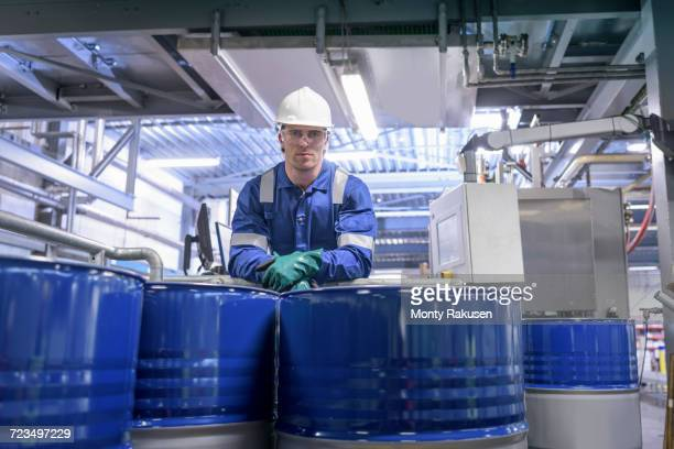 Portrait of worker with process machinery in oil blending factory