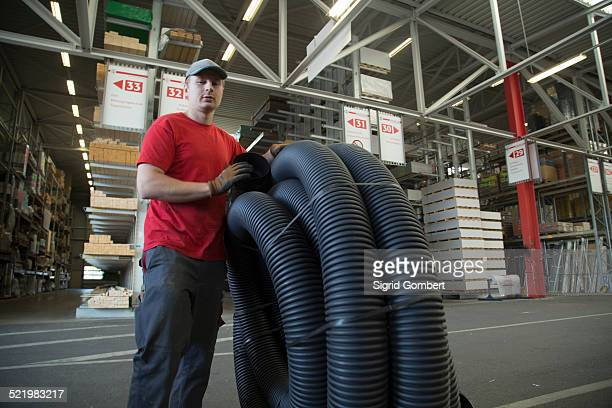 portrait of worker with rolled up piping in hardware store warehouse - sigrid gombert stock pictures, royalty-free photos & images