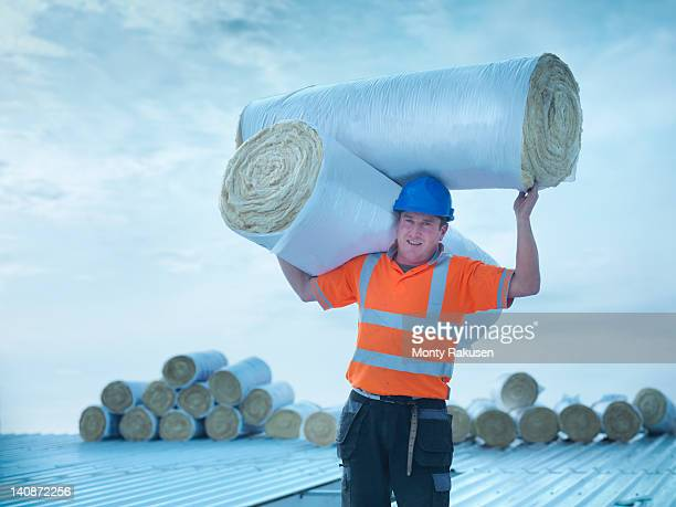 Portrait of workman carrying rolls of insulation to install into factory roof