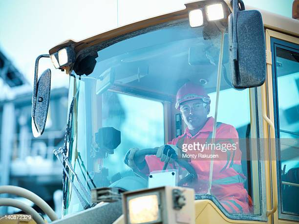 Portrait of workman driving industrial digger on quarry site