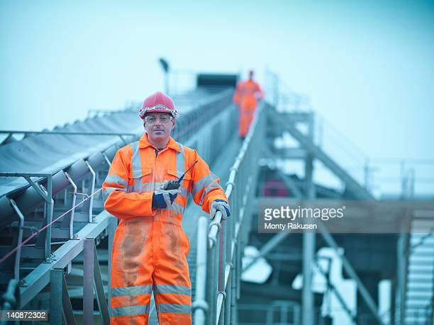 Portrait of workman in reflective clothing holding walkie talkie on steps of screening conveyor at quarry