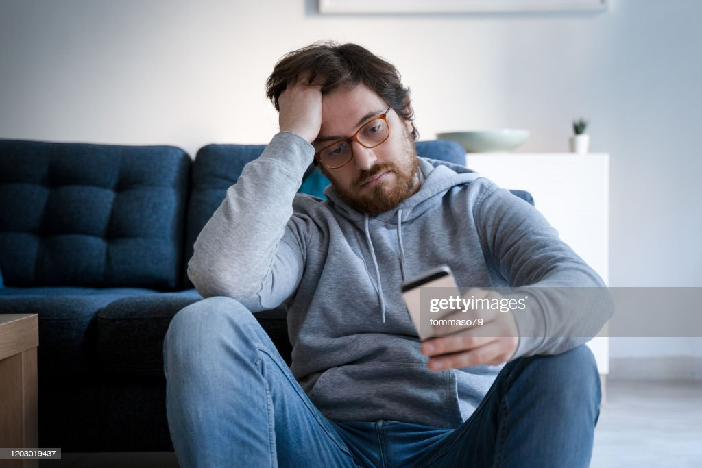 Portrait of worried guy holding cellphone at home : Stock Photo