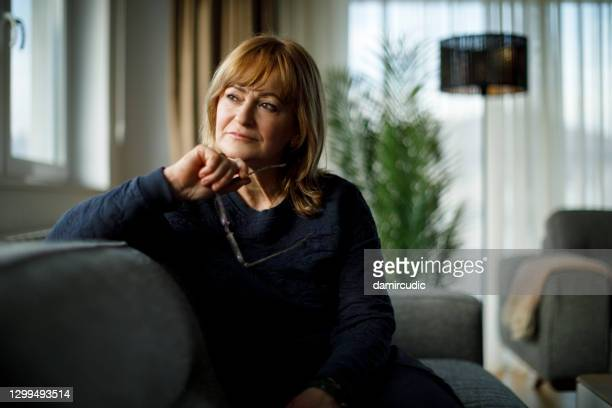 portrait of worried senior woman sitting on sofa at home - blame stock pictures, royalty-free photos & images