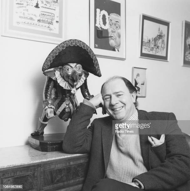 Portrait of writer and satirist Alan Coren editor of 'Punch' magazine sitting next to a 'Punch' character figurine February 1983