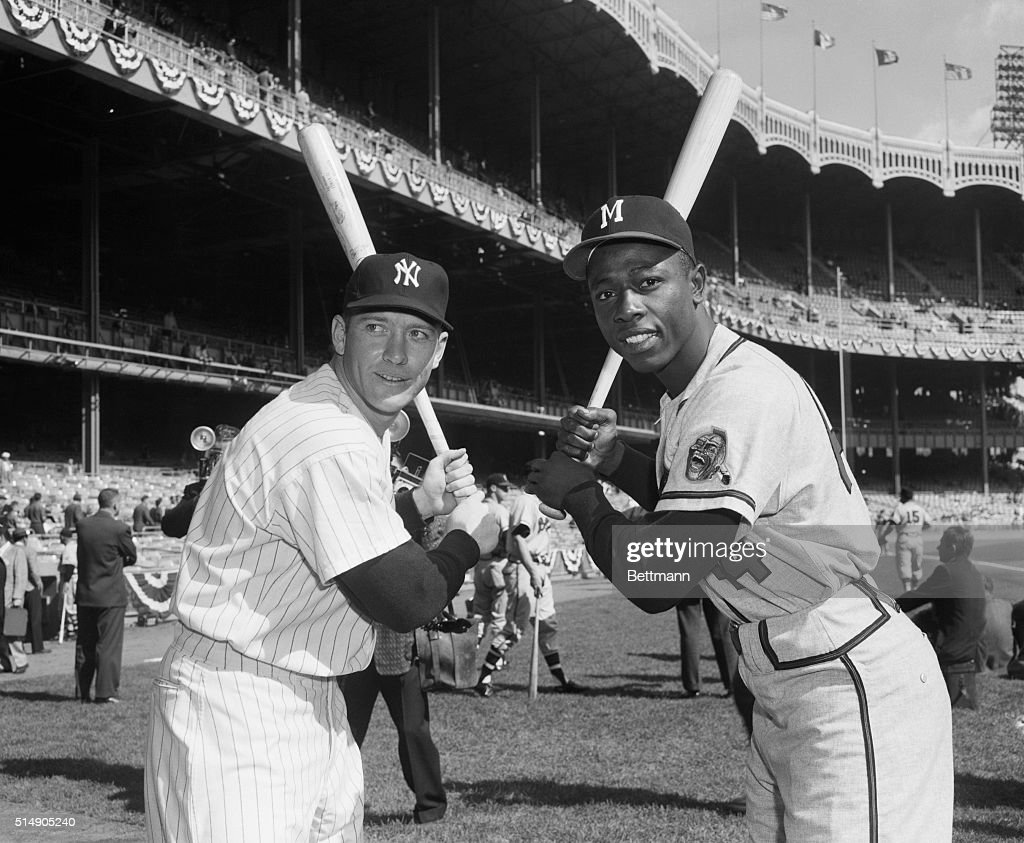 Portrait of Yankee outfielders Mickey Mantle and Hank Aaron posing in batting stance.