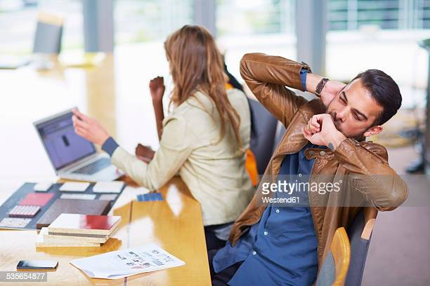 Portrait of yawning businessman in a meeting