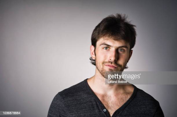 portrait of young adult caucasian male wearing long sleeve t shirt - smirking stock pictures, royalty-free photos & images