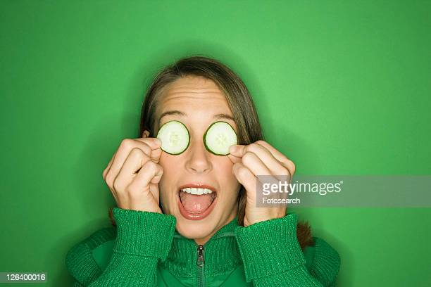 portrait of young adult caucasian woman on green background holding cucumber slices over her eyes. - seulement des adultes photos et images de collection