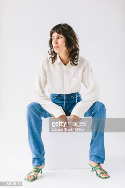 portrait of young adult caucasian woman sitting - casual clothing imagens e fotografias de stock
