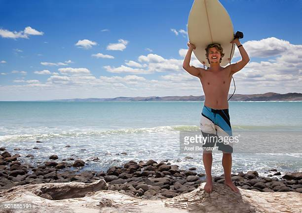 Portrait of young adult male surfer holding up surfboard
