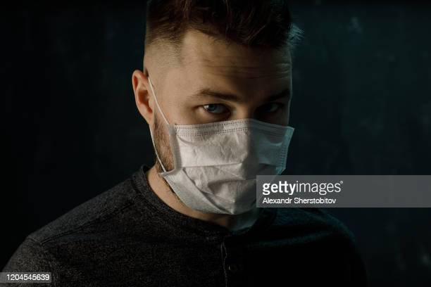 portrait of young adult man in medical mask. colored light - coronavirus stock pictures, royalty-free photos & images
