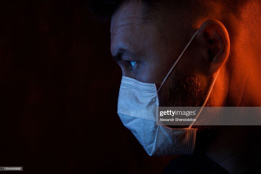 Portrait of young adult man in medical mask. Colored light : Stock Photo