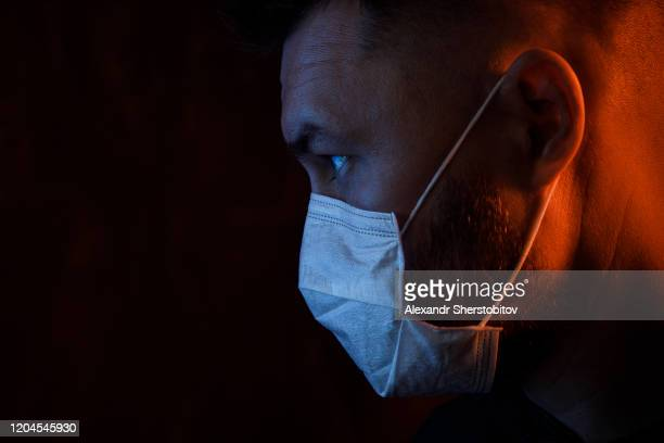 portrait of young adult man in medical mask. colored light - coronavirus foto e immagini stock