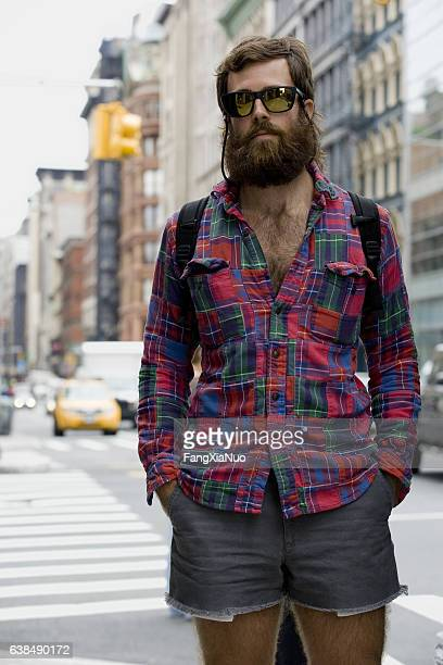 portrait of young adult man with beard in downtown city - homme poilu photos et images de collection