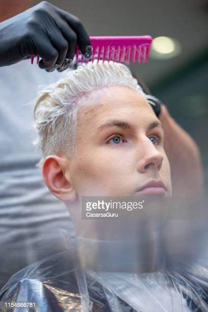 porträt des jungen erwachsenen mannes mit gebleicht haar im haarbehandlungs-und schönheitssalon - gebleichtes haar stock-fotos und bilder