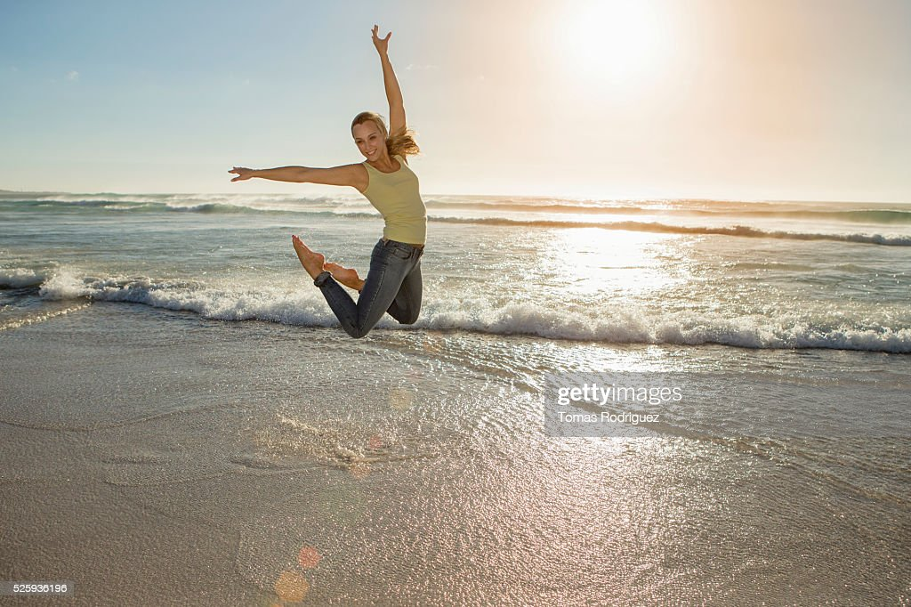 Portrait of,, young adult woman jumping on beach : Stock Photo