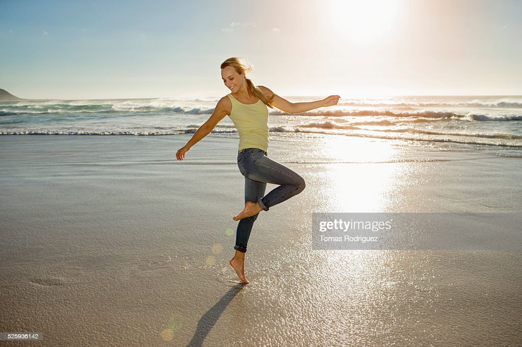Portrait of young adult woman on beach standing on one leg : Stock Photo