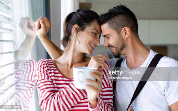 portrait of young affectionate couple standing indoors by window at home. - love is blind stock pictures, royalty-free photos & images
