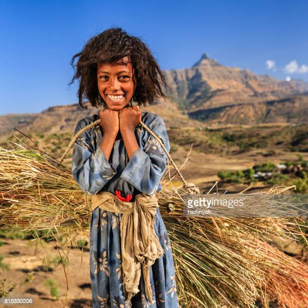 portrait of young african girl carrying straw, east africa - child labour stock pictures, royalty-free photos & images