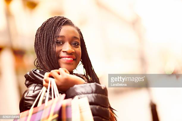 Portrait of young African woman with shopping bags