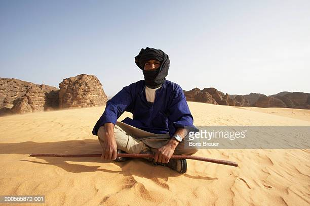 Portrait of young Algerian man sitting on desert, holding stick