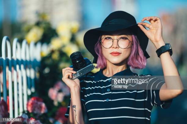 portrait of young and beautiful woman while holding camera - funky stock pictures, royalty-free photos & images