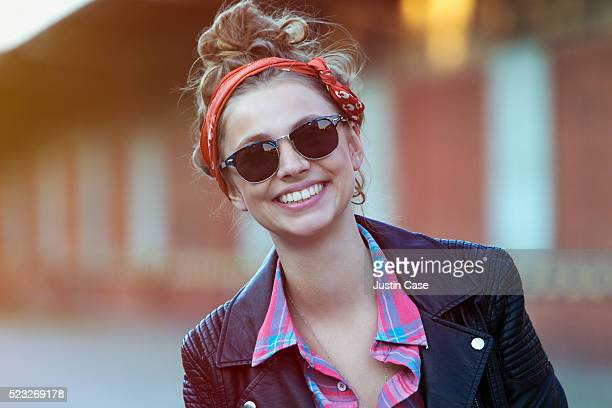 Portrait of young and smiling brunette woman standing in urban environment