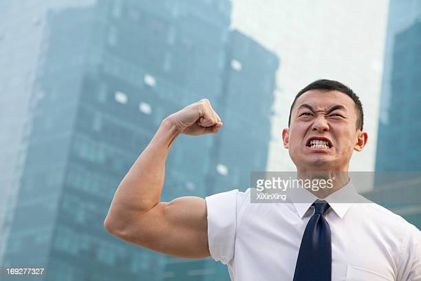 Portrait of young angry businessman flexing muscles