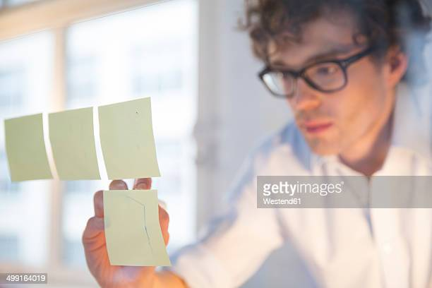 Portrait of young architect fastening memos on glass pane in office
