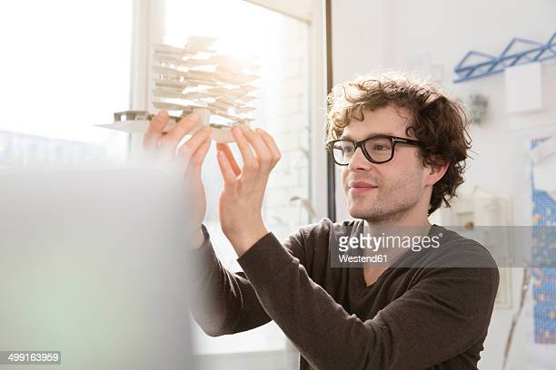 Portrait of young architect looking at architectural model