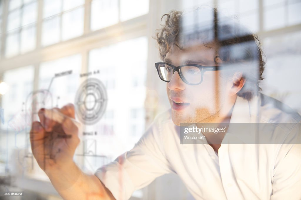 Portrait of young architect marking construction plan in office : Stock Photo