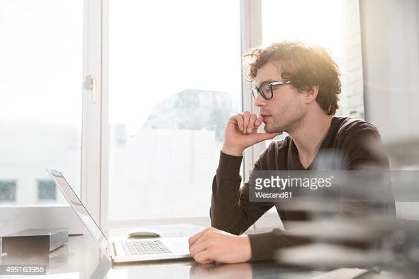 Portrait of young architect using laptop in his office