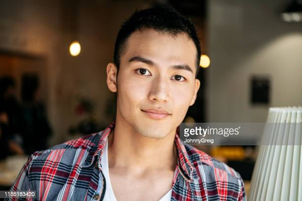 portrait of young asian businessman in check shirt - chinese ethnicity stock pictures, royalty-free photos & images