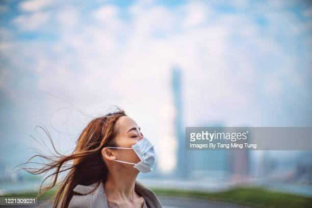 portrait of young asian lady with closed eyes wearing a face mask to protect and prevent from the spread of viruses in the city - healthcare stock pictures, royalty-free photos & images