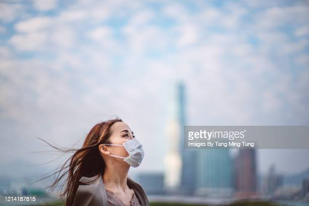 portrait of young asian lady with face mask to protect and prevent from the spread of viruses in the city - pollution stock pictures, royalty-free photos & images