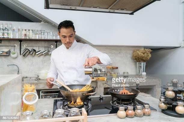 Portrait of young Asian man chef preparing spaghetti in kitchen.