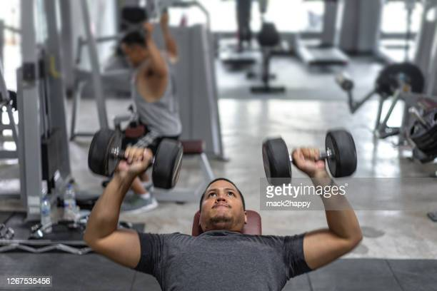 portrait of young asian  man muscular built athlete  working out in gym, lying holding two dumbbell - skinhead stock pictures, royalty-free photos & images