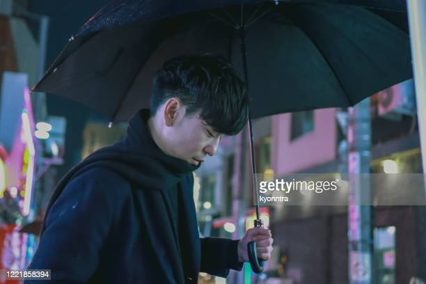 portrait of young asian man under raining in the night city - kyonntra stock pictures, royalty-free photos & images